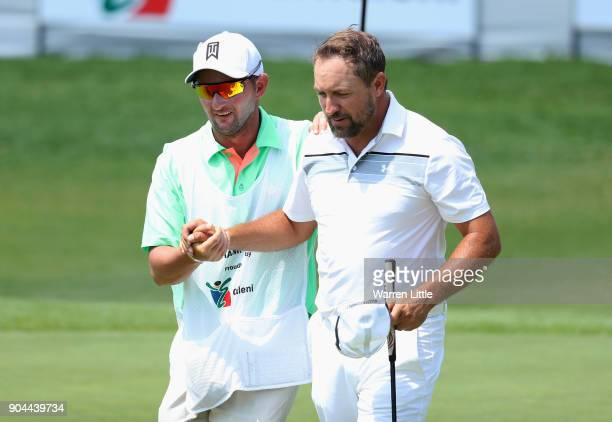 Darren Fichardt of South Africa shakes hands with his caddie on the 18th green during day three of the BMW South African Open Championship at...