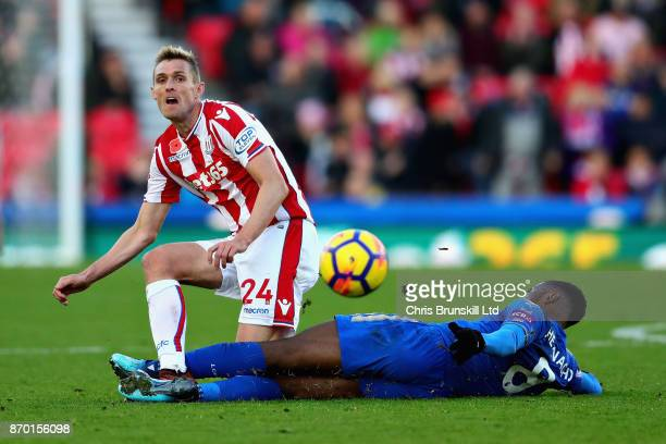 Darren Fletcher of Stoke City passes the ball as he is challenged by Kelechi Iheanacho of Leicester City during the Premier League match between...