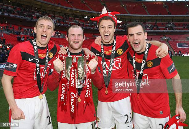 Darren Fletcher Wayne Rooney Jonny Evans and Darron Gibson of Manchester United pose with the Carling Cup trophy after the Carling Cup Final match...