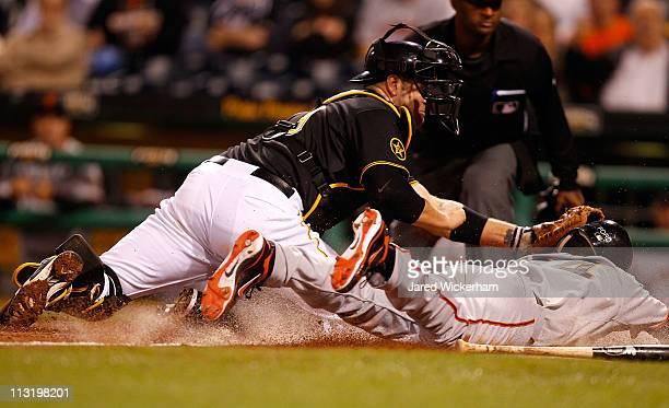 Darren Ford of the San Francisco Giants slides safely past Chris Synder of the Pittsburgh Pirates to score the gamewinning run during the game on...