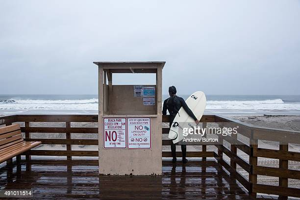 Darren Gallo who lives one block from the beach waits for his friend after two hours of surfing during the potential build up to Hurricane Joaquin on...