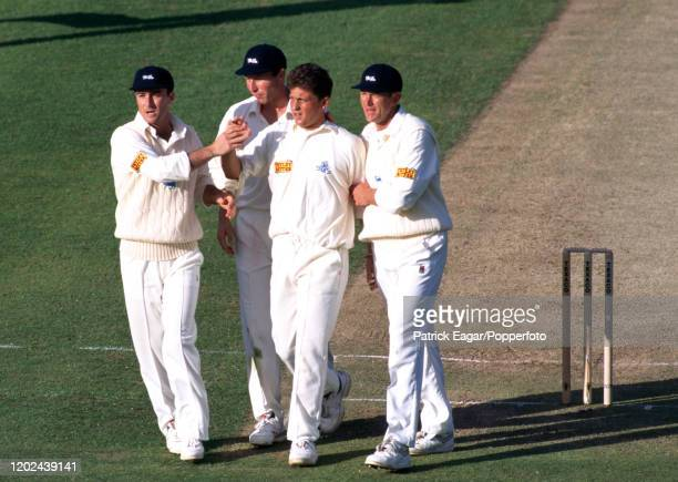 Darren Gough of England is congratulated by teammates Graham Thorpe Mike Atherton and Alan Wells on the wicket of West indies captain Richie...