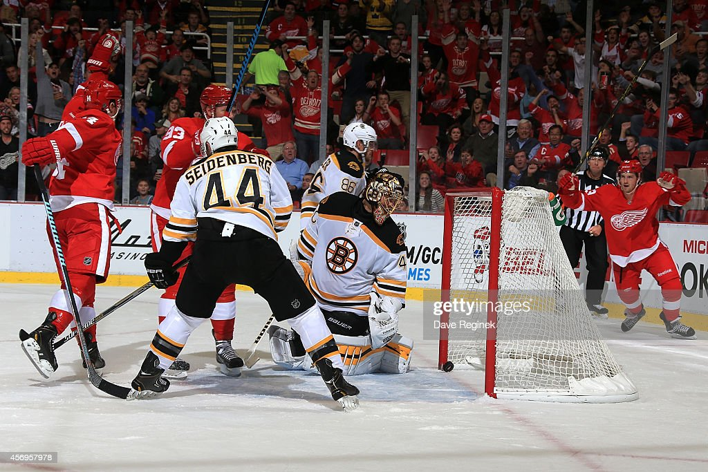 Darren Helm #43 and Gustav Nyquist #14 of the Detroit Red Wings celebrate after connecting on a power-play goal as goalie Tuukka Rask #40 of the Boston Bruins looks behind him at the puck in the net during the NHL season opener on October 9, 2014 at Joe Louis Arena in Detroit, Michigan.