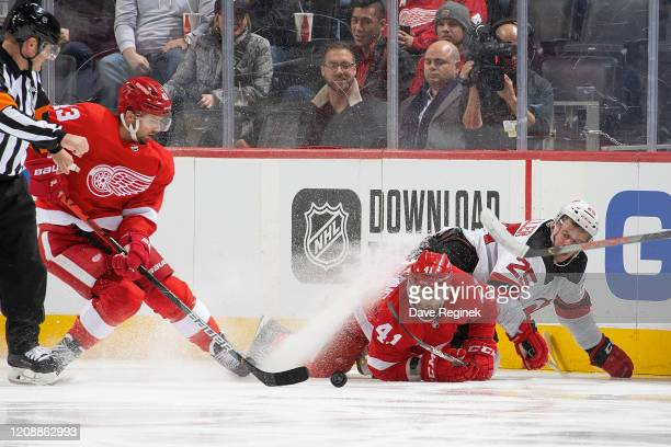 Darren Helm and Luke Glendening of the Detroit Red Wings battles for the puck with Mirco Mueller of the New Jersey Devils during an NHL game at...
