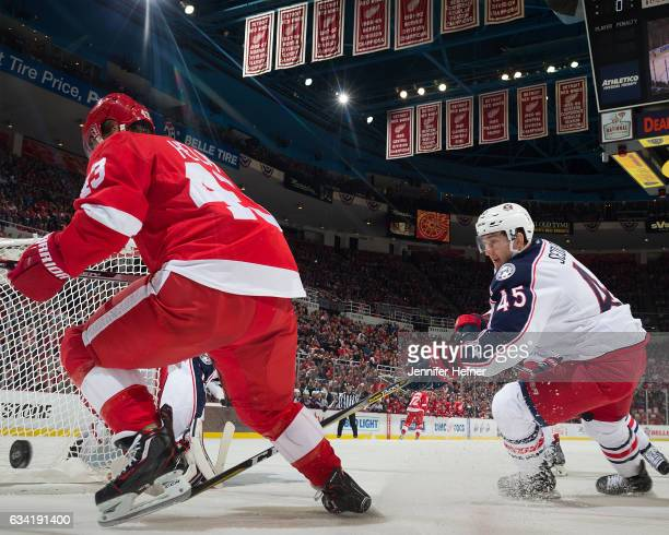 Darren Helm of the Detroit Red Wings and Lukas Sedlak of the Columbus Blue Jackets battle for the puck behind the net during an NHL game at Joe Louis...