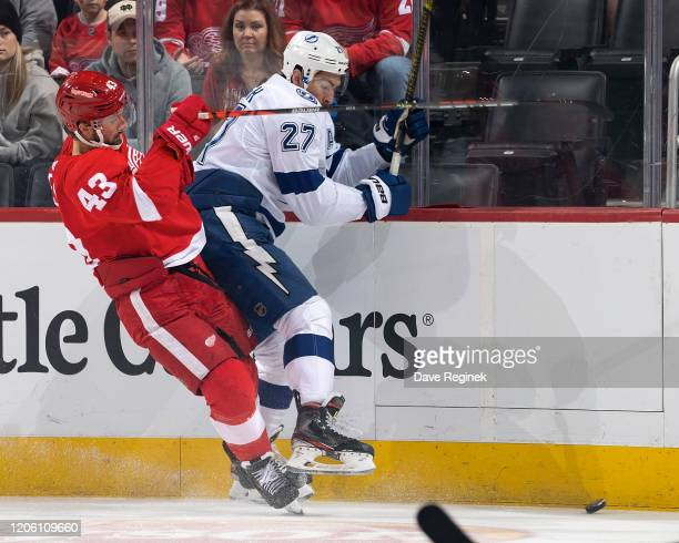 Darren Helm of the Detroit Red Wings battles along the boards for the puck with Ryan McDonagh of the Tampa Bay Lightning during an NHL game at Little...