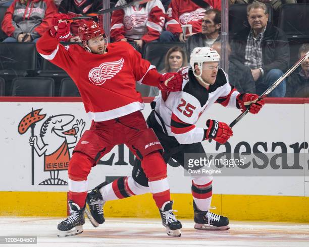 Darren Helm of the Detroit Red Wings battles for position along the boards with Mirco Mueller of the New Jersey Devils during an NHL game at Little...