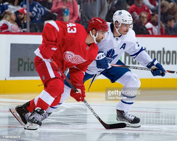 Darren Helm of the Detroit Red Wings battles for the puck with Auston Matthews of the Toronto Maple Leafs during an NHL game at Little Caesars Arena...