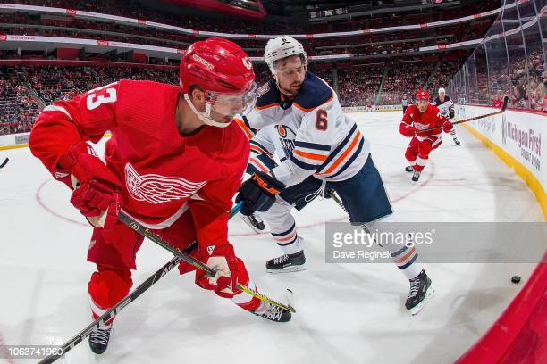 Darren Helm of the Detroit Red Wings battles in the corner for the puck with Adam Larsson of the Edmonton Oilers during an NHL game at Little Caesars...