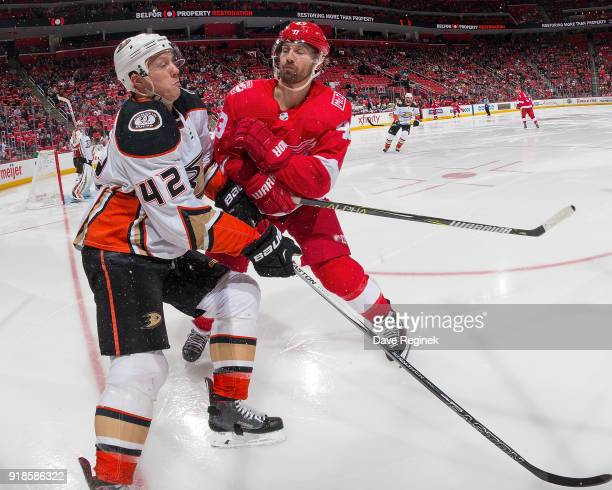 Darren Helm of the Detroit Red Wings body checks Josh Manson of the Anaheim Ducks during an NHL game at Little Caesars Arena on February 13 2018 in...