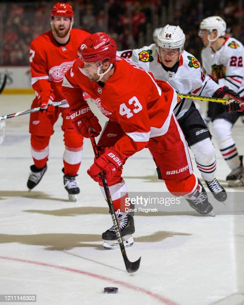 Darren Helm of the Detroit Red Wings controls the puck in front of David Kampf of the Chicago Blackhawks during an NHL game at Little Caesars Arena...