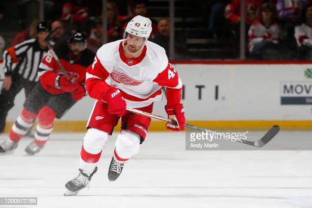 Darren Helm of the Detroit Red Wings keeps his eye on the puck during the game against the New Jersey Devils at the Prudential Center on February 13...