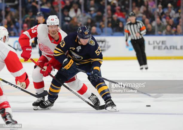 Darren Helm of the Detroit Red Wings knocks the puck off the stick of Jeff Skinner of the Buffalo Sabres as he skates up ice during the second period...