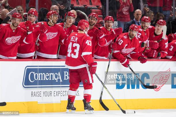 Darren Helm of the Detroit Red Wings pounds gloves with teammates on the bench following his third period goal during an NHL game against the...
