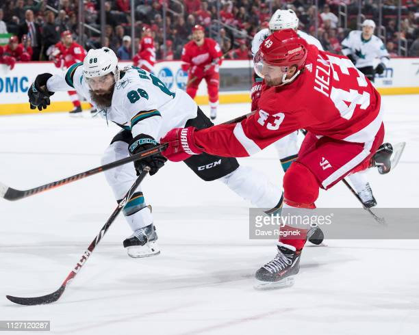 Darren Helm of the Detroit Red Wings shoots the puck past the defense of Brent Burns of the San Jose Sharks to score a first period goal during an...