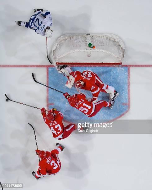 Darren Helm of the Detroit Red Wings skates after a loose puck next to teammates Valtteri Filppula Alex Biega and goaltender Jonathan Bernier as...