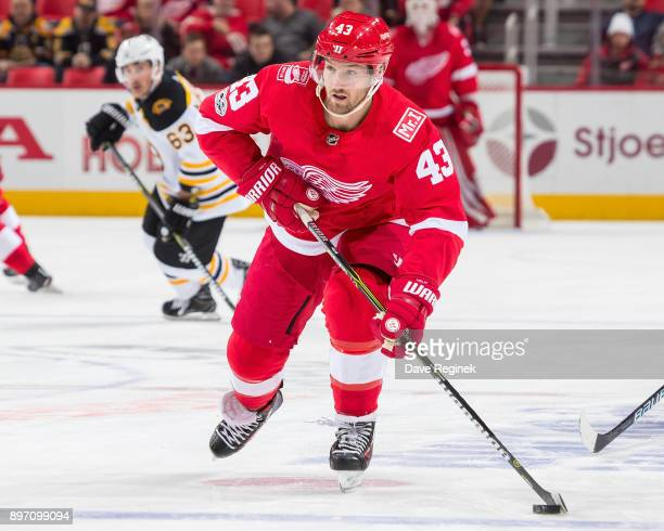 Darren Helm of the Detroit Red Wings skates up ice with the puck against the Boston Bruins during an NHL game at Little Caesars Arena on December 13...