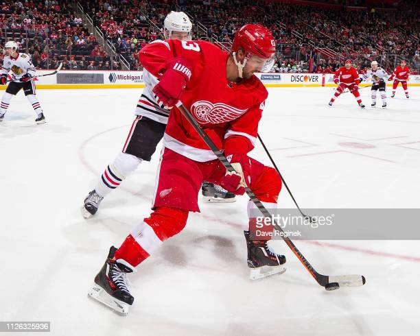Darren Helm of the Detroit Red Wings skates with the puck followed by Connor Murphy of the Chicago Blackhawks during an NHL game at Little Caesars...