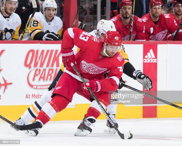 Darren Helm of the Detroit Red Wings skates with the puck in front of Brian Dumoulin of the Pittsburgh Penguins during an NHL game at Little Caesars...