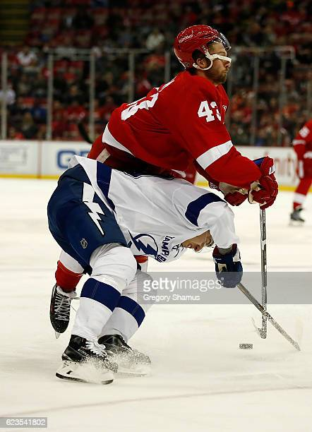 Darren Helm of the Detroit Red Wings takes a third period hit from Nikita Nesterov of the Tampa Bay Lightning at Joe Louis Arena on November 15 2016...