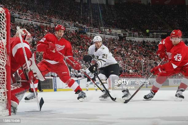 Darren Helm of the Detroit Red Wings takes the puck while Jonathan Ericsson defends Steve Ott of the Dallas Stars and Joey MacDonald tends net during...