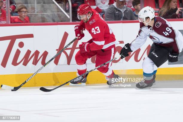 Darren Helm of the Detroit Red Wings tries to skate past Samuel Girard of the Colorado Avalanche during an NHL game at Little Caesars Arena on...