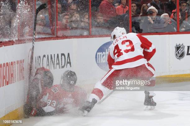 Darren Helm of the Detroit Red Wings trips Christian Jaros of the Ottawa Senators into the end boards leading to a second period penalty at Canadian...