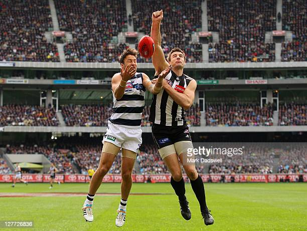 Darren Jolly of the Magpies punches the ball clear of Jimmy Bartel of the Cats during the 2011 AFL Grand Final match between the Collingwood Magpies...