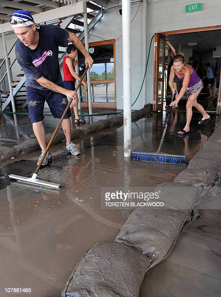 Darren Kelly and Caroline Fisher clean foul smelling mud from the recently submerged Spinnakers bar and restaurant on the banks of the swollen...