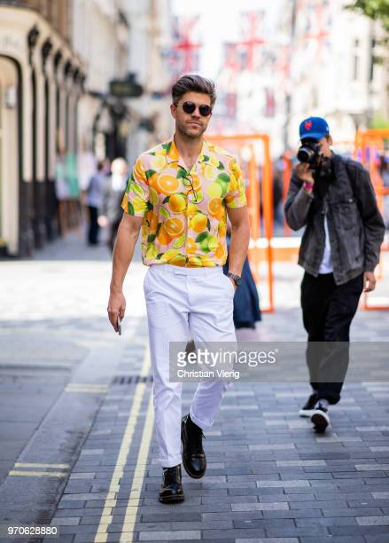 Darren Kennedy wearing button shirt with fruit print white pants is seen during London Fashion Week Men's June 2018 on June 9 2018 in London England