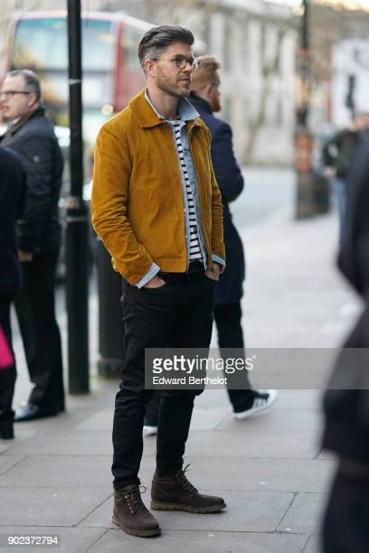 Darren Kennedy wears glasses a yellow jacket a striped top a blue shirt during London Fashion Week Men's January 2018 at on January 7 2018 in London...