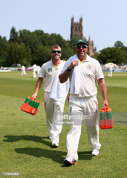 Darren Lehmann coach of Australia and David Warner of Australia run drinks out to the players during day three of the Tour Match between...