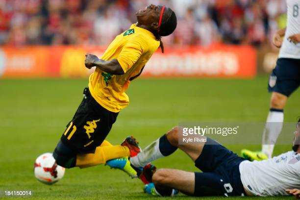 Darren Mattocks of Jamaica has his feet taken out by Brad Evans of the US Men's National Soccer Team in the first half at Sporting Park on October 11...