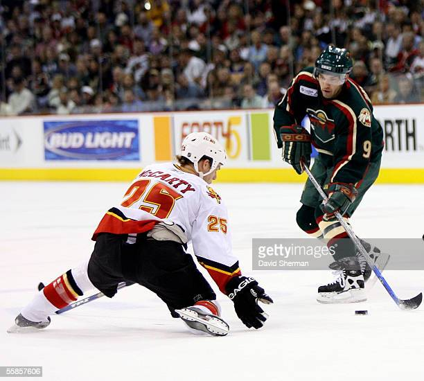 Darren McCarty of the Calgary Flames tries to stop the pass from Alexandre Daigle of the Minnesota Wild during their season opening game on October 5...