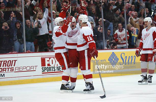 Darren McCarty of the Detroit Red Wings celebrates his third goal of the game for the 'hat trick' with teammates Sergei Fedorov and Kirk Maltby...