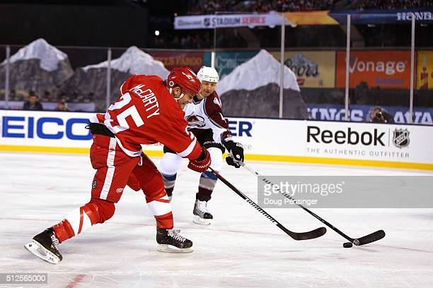 Darren McCarty of the Detroit Red Wings takes a shot against Rob Blake of the Colorado Avalanche during the 2016 Coors Light Stadium Series Alumni...
