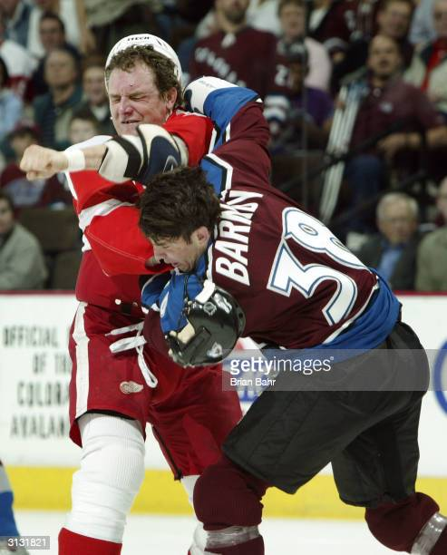 Darren McCarty of the Detroit Red Wings takes a swing at Matthew Barnaby of the Colorado Avalanche as they square off for a fight in the first period...