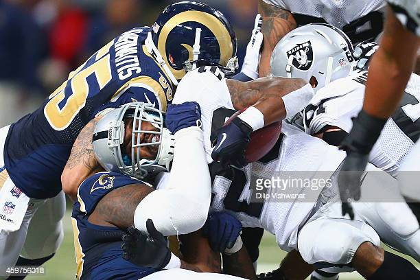 Darren McFadden of the Oakland Raiders is tackled by James Laurinaitis of the St Louis Rams in the first quarter at the Edward Jones Dome on November...
