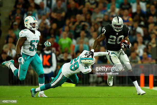 Darren McFadden of the Oakland Raiders is tackled by Will Davis of the Miami Dolphins during the NFL match between the Oakland Raiders and the Miami...