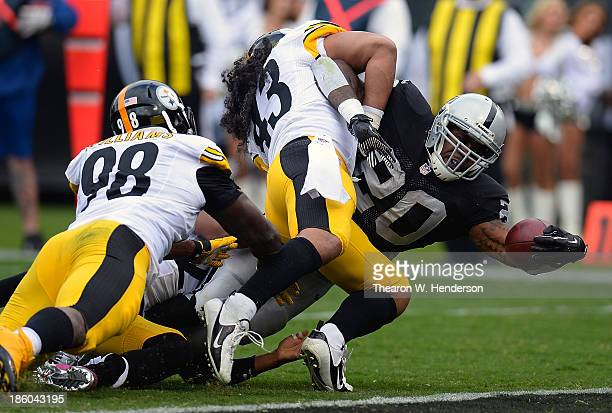 Darren McFadden of the Oakland Raiders reaches out to scores on a seven yard touchdown run while being tackled by Troy Polamalu of the Pittsburgh...