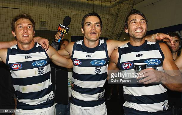 Darren Milburn Matthew Scarlett and Corey Enright of the Cats sing the song in the rooms after winning the round five AFL match between the Hawthorn...