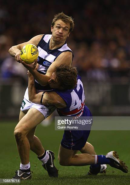Darren Milburn of the Cats is tackled by Liam Picken of the Bulldogs during the round 20 AFL match between the Western Bulldogs and the Geelong Cats...