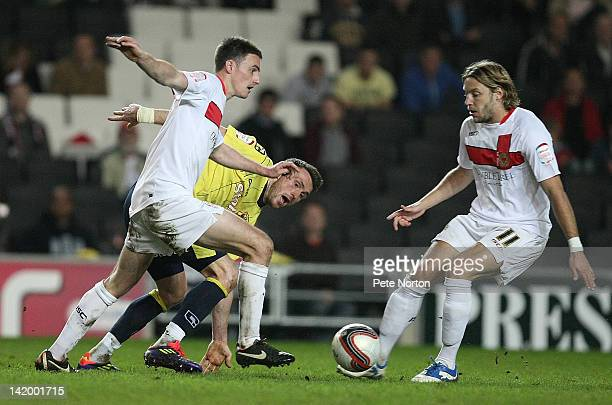 Darren Potter of Milton Keynes Dons looks to move away from Lee Miller of Carlisle United as team mate Alan Smith looks on during the League One...