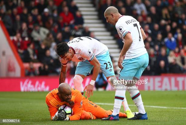 Darren Randolph of West Ham United is congraulated by Jose Fonte of West Ham United and Sofiane Feghouli of West Ham United are saving Benik Afobe of...