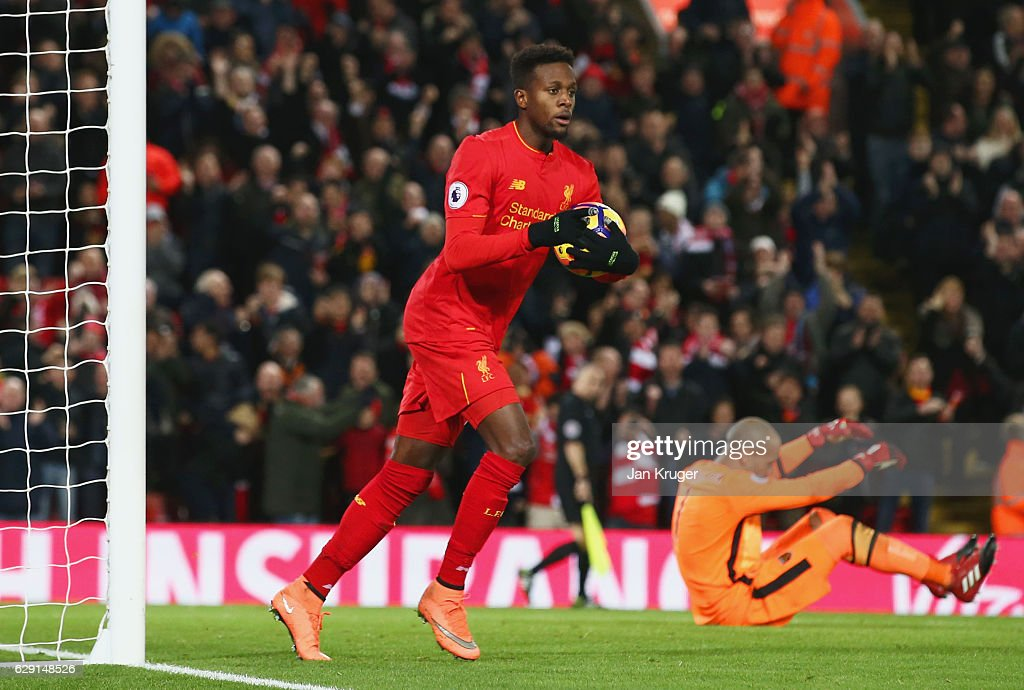 Darren Randolph of West Ham United looks dejected as Divock Origi of Liverpool celebrates as he scores their second goal during the Premier League match between Liverpool and West Ham United at Anfield on December 11, 2016 in Liverpool, England.