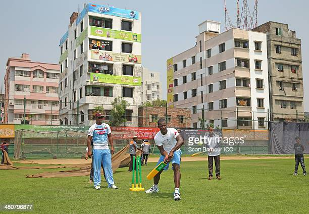 Darren Sammy captain of the West Indies bats and Johnson Charles wicketkeeps as they play a game of cricket with children during an ICC Thinkwise CSR...