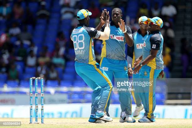 Darren Sammy Mervin Matthew and Liam Sebastien of St Lucia Zouks celebrate a wicket during a match between Jamaica Tallawahs and St Lucia Zouks as...
