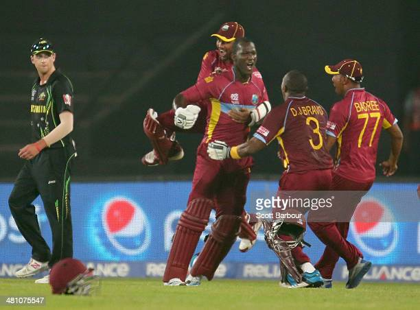 Darren Sammy of the West Indies is congratulated by his teammates after hitting the winning runs as James Muirhead of Australia looks on during the...