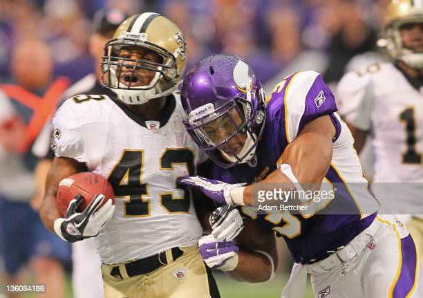 Darren Sproles of the New Orleans Saints carries the ball for a gain while Jamarca Sanford of the Minnesota Vikings pushes him out of bounds at the...