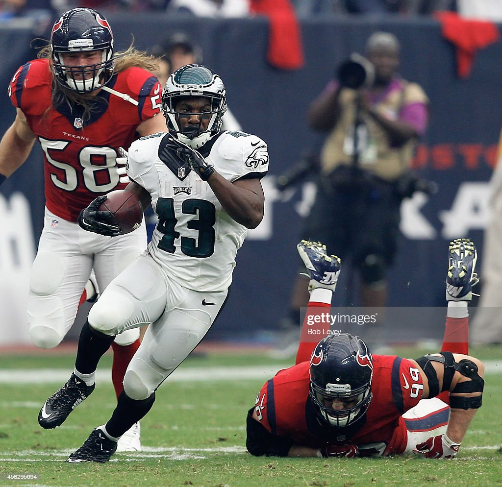 Darren Sproles #43 of the Philadelphia Eagles breaks a tackle attempt by J.J. Watt #99 of the Houston Texans at Reliant Stadium on November 2, 2014 in Houston, Texas.